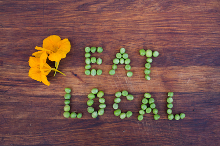 organic farm: Sign Eat Local made of green peas on wooden background. Nasturtium flowers on a side. Organic vegetable produce at a farm. Stock Photo