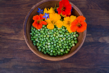 edible leaves: Green peas and colorful edible flowers in clay bowl on wooden background. Bright nasturtium flowers with leaves and borage. Healthy organic food at a local farm.