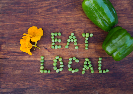 organic peppers sign: Sign Eat Local made of green peas on wooden background. Edible flowers and peppers on a side. Organic vegetable produce at a farm.