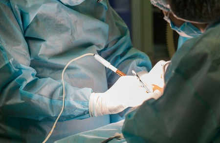 Close-up image of sugeon and his assistant performing cosmetic surgery on in hospital operating room. Doctor holding surgical instrument. Breast augmentation, enlargement, enhancement