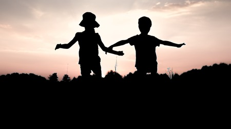 fraternal: Silhouettes of children jumping off a cliff at sunset. Little boy and girl jump raising hands up high. Brother and sister having fun in summer. Friendship, freedom concept. Fraternal twins on vacation in mountains.