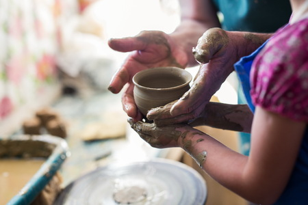the elderly tutor: Senior potter teaching a little girl the art of pottery. Child working with clay, Creating ceramic pot on sculpting wheel. Concept of mentorship, generations. Arts lessons, pottery workshop for kids