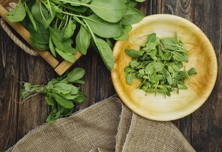 Rustic wooden tray with fresh organic local spinach leaves plants on a table. Wooden plate with greens, arugula. First spring summer crop. Vegetarian vegan healthy food. Grow your own, eat local