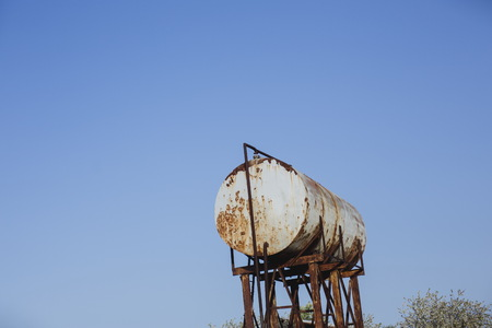 Rusty water tower. Old water cistern canister barrel tank