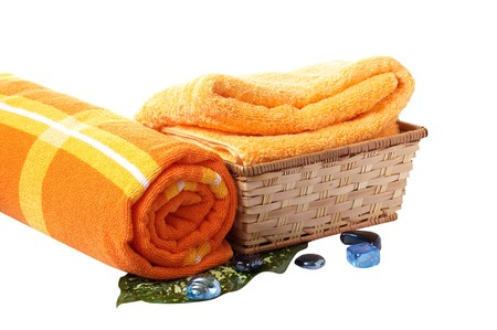Towels with wonderful stones,green leaf and basket isolated on a white background. photo