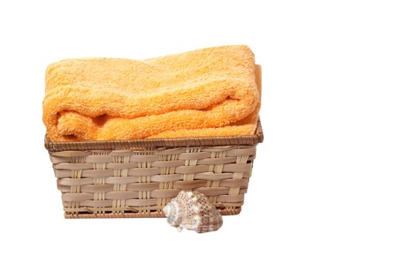 Towel in the basket and seashell isolated on a white background. photo