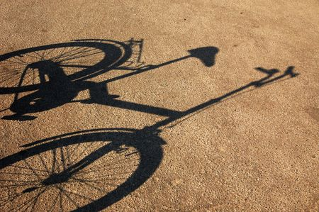 Shade of a bicycle on a cracked asphalt.
