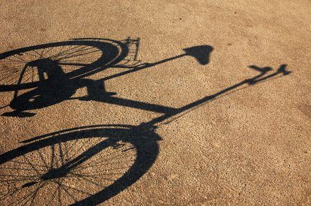 retro bicycle: Sombra de una bicicleta sobre un asfalto resquebrajado. Foto de archivo