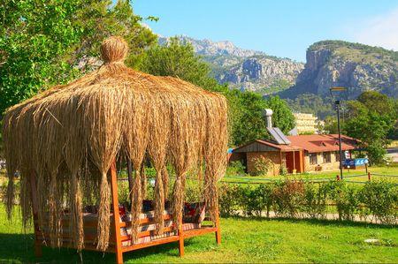 tuinhuis: Nice zomerhuis en hoge bergen in resort. Turkije. Stockfoto