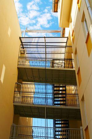 Fire escape  against blue cloudy sky. Stock Photo - 5115364