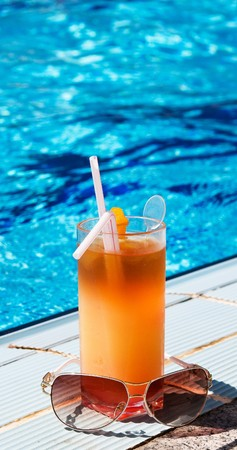 Sunglass and tasty cocktail with lemon next to swimming pool.