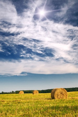 Three haystack and wonderful clouds.