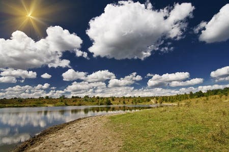 Lake, meadow and blue sky in the begining autumn. photo