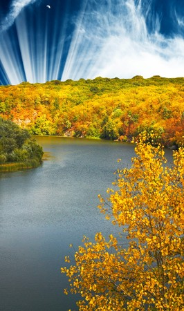 Amazing autumn sunset above of river ,forest and mountains.  photo