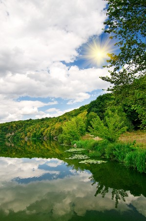 Wonderful sun above autumnal lake and forest. photo