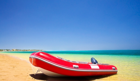 lifeboat: Single red inflatable lifeboat on the beach
