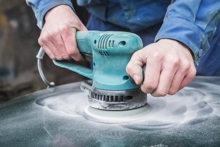 repaint: Sanding polishing bumper car at automobile