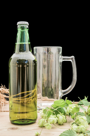 bottle of beer with hop and wheat and a glass