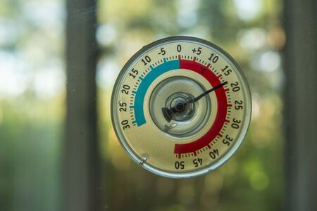 a thermometer of temperature outside the window that hangs on the window in the house 写真素材