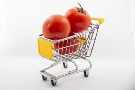 small cart with tomatoes on a white background