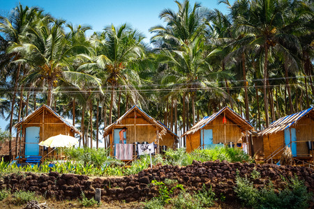 wooden bungalows among coconat palm trees Editorial