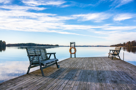 duckboards: jetty with benches at the lake in the evening