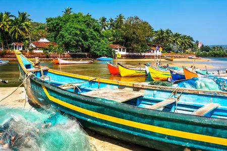 pesca: brillantes barcos de madera de pesca en la orilla del r�o en el tr�pico con palmeras y cielo azul. Goa, India