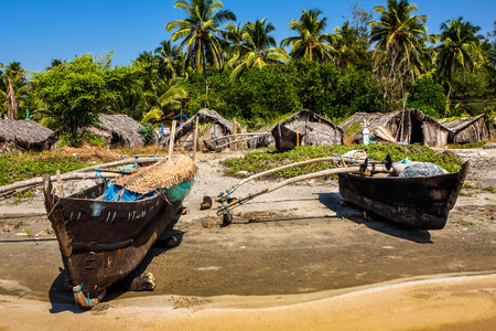 old fishing boat on the beach  in tropical with palms, huts and blue sky