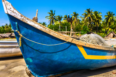 old fishing boat on the beach  in tropical climat with palms and blue sky