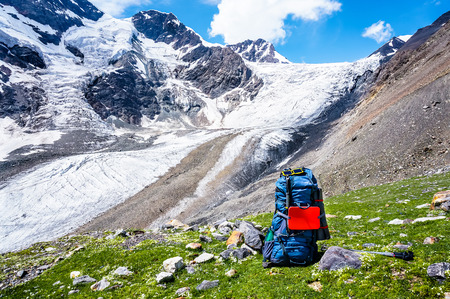 Big backpack on a background of mountains, in front of the pass and the glacier. Summer trekking hike in scenic Caucasus mountains, Bezengi region, Kabardino-Balkaria, Russia.
