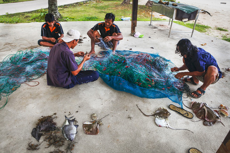 Ko Chang Island, Thailand - April 09, 2011: - thai fishermen sorting their catch on the shore Editorial