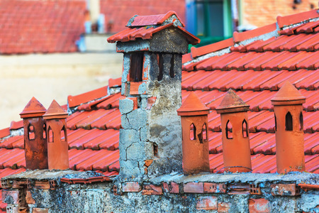 Architecture details of the house with old chimney and tile roof on the background