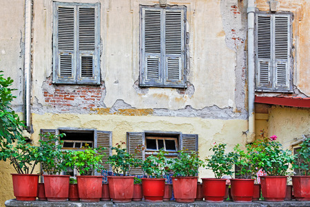 View of a wall of an old house with wooden shutters and large red flower pots Imagens