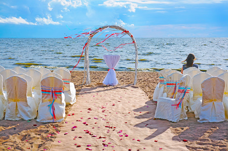 Wedding ceremony place in modern european style with the arch on the beach and a girl sitting alone Imagens