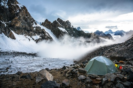 Lonely mountaineers camp in very high snowy moutains beside glacier. Picture was taken during a trekking hike in the amazing and gorgeous Caucasus mountains, Bezengi region, Kabardino-Balkaria, Russia