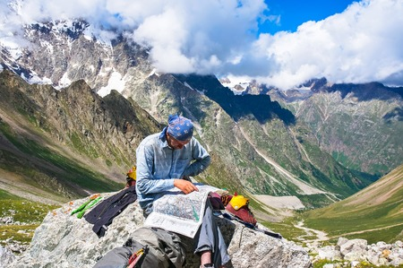 Hiker in the mountains watching the map on a halt. Picture was taken during a trekking in the scenic Caucasus mountains, Bezengi region, Kabardino-Balkaria, Russia Editorial