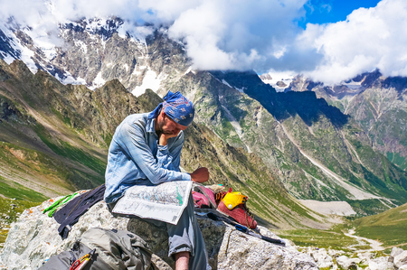 Hiker in the mountains watching the map on at rest. Picture was taken during a trekking in the scenic Caucasus mountains, Bezengi region, Kabardino-Balkaria, Russia