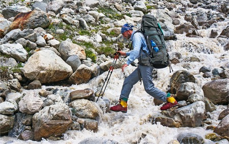CAUCASUS, KABARDINO-BALKARIA, RUSSIA - JULY 22, 2014: The traveler passes over the rocks through a mountain stream Editorial