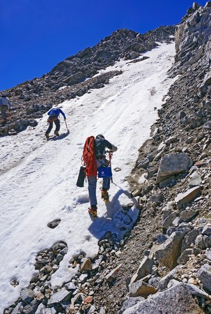 CAUCASUS, KABARDINO-BALKARIA, RUSSIA - JULY 23, 2014:  Group of mountaineers ascent to the mountain on a snow-covered slope portion