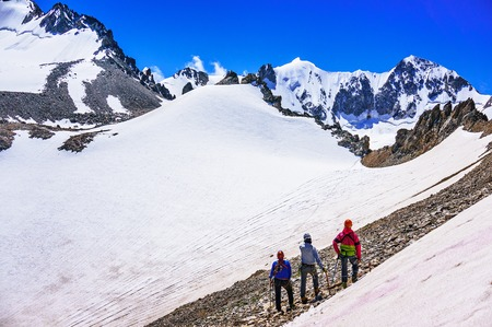 CAUCASUS, KABARDINO-BALKARIA, RUSSIA - JULY 23, 2014:  Group of climbers looking at snow-capped mountains and glacier