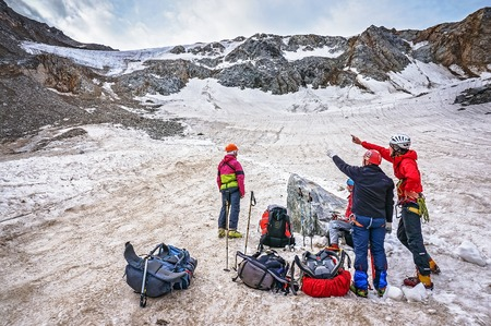 CAUCASUS, KABARDINO-BALKARIA, RUSSIA - JULY 23, 2014:  Group of climbers discusses the route of the mountain pass