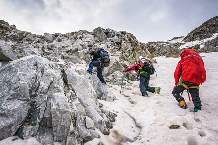 CAUCASUS, KABARDINO-BALKARIA, RUSSIA - JULY 25, 2014:  Group of climbers ascent to the mountain on a complex slope is composed of rock and snow