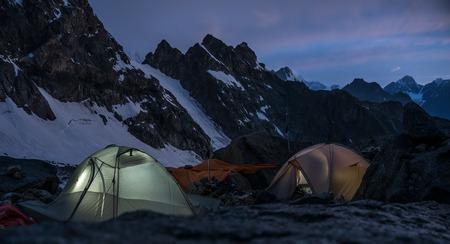 montañas nevadas: Montañeros campamento por la noche en muy altas montañas nevadas.