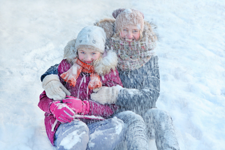Family - mother with her daughter play in the snow and enjoying winter