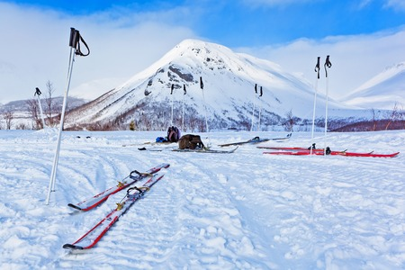 ski and ski poles in the winter mountains in the background