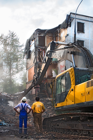MOSCOW, RUSSIA - September 03, 2009:  excavator demolishes the old soviet apartment house in Moscow Imagens
