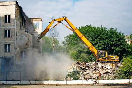 dismantling: excavator demolishes the old soviet apartment house in Moscow