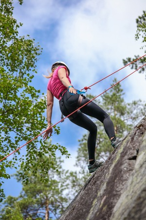 Pretty young woman practicing climbing on natural rocks spending so her active leisure Imagens