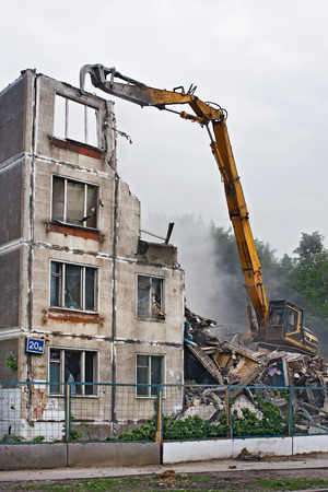 Excavator destroys the old soviet apartment house