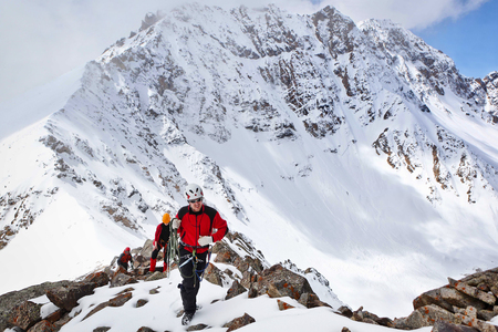 Dugoba, Pamiro-Alay, Kyrgyzstan - May 02, 2013: Group of mountaineers ascent to the mountain using the rope on a complex slope is composed of rock and snow